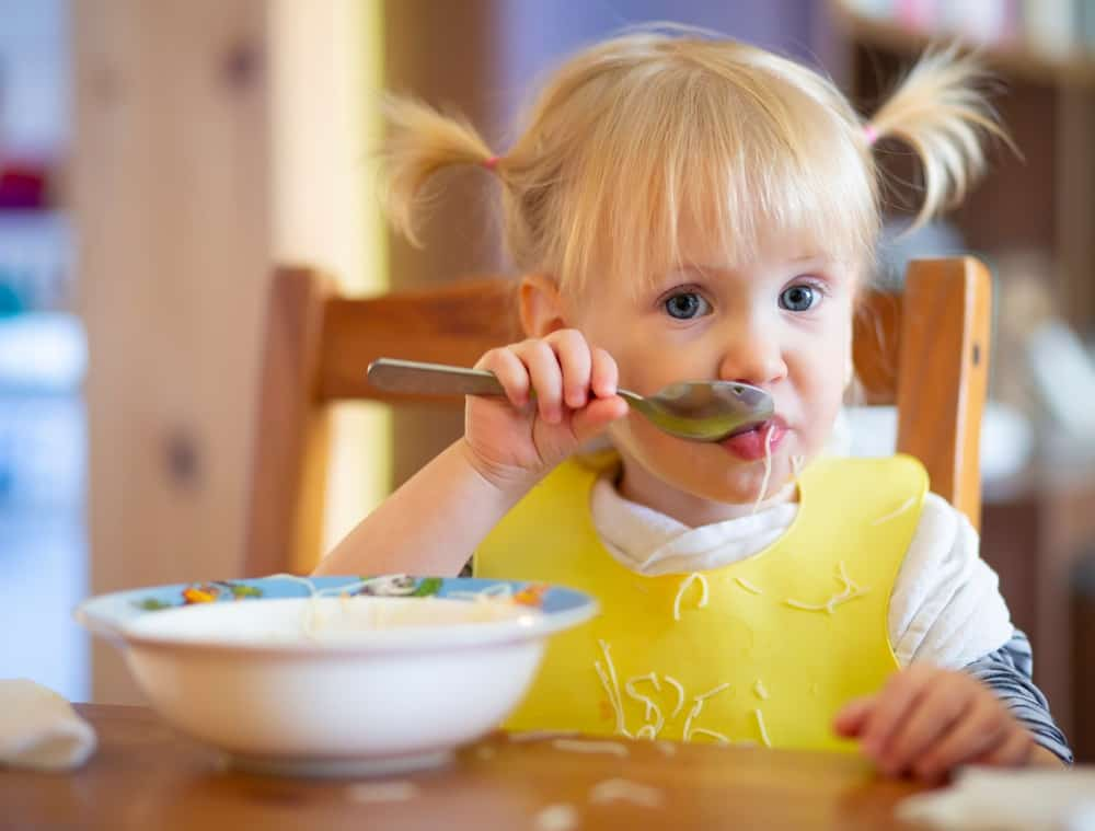 Cute child eating with spoon at table