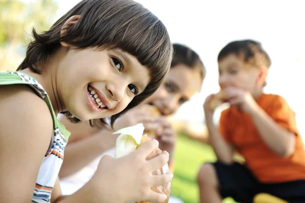 Happy children eating together in nature